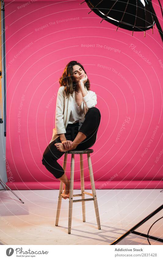 Frau auf Hocker im Studio hübsch Porträt Jugendliche sitzen Augen geschlossen schön Erwachsene Körperhaltung Lächeln Beautyfotografie attraktiv Model Mensch