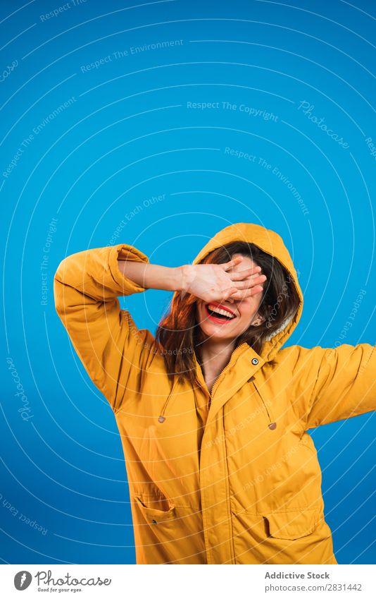 Fröhliche Frau in gelber Jacke hübsch Porträt Jugendliche Lächeln Schließfläche Hand schön Erwachsene Körperhaltung Beautyfotografie attraktiv Model Mensch