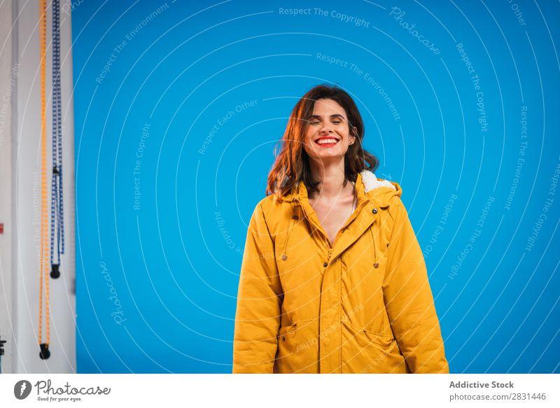 Fröhliche Frau in gelber Jacke hübsch Porträt Jugendliche Lächeln schön Erwachsene Körperhaltung Beautyfotografie attraktiv Model Mensch genießen elegant