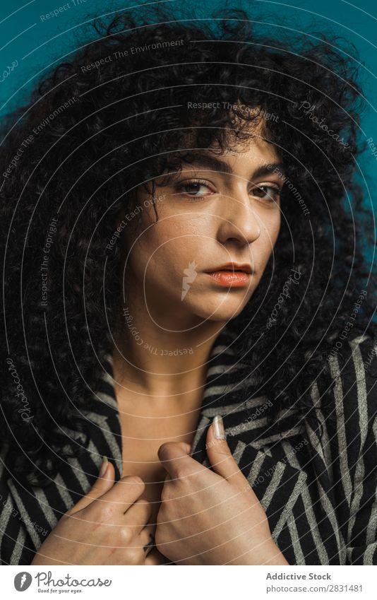 Lockige Frau, die im Studio posiert. hübsch Porträt Jugendliche lockig Behaarung brünett schön Erwachsene Körperhaltung Beautyfotografie attraktiv Model Mensch