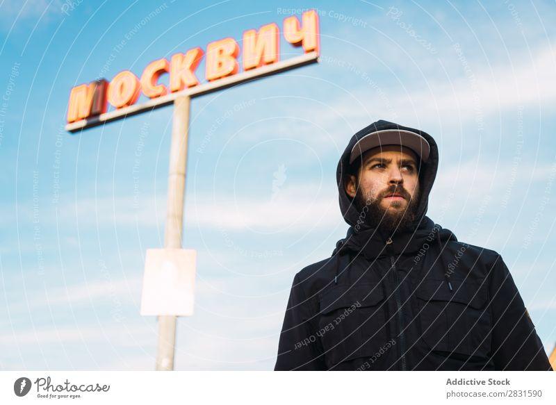Mann, der auf der Straße an der Säule steht. gutaussehend Großstadt Zeichen Post Wegsehen Jugendliche Stadt Lifestyle lässig Mode Stil Erwachsene modern Mensch