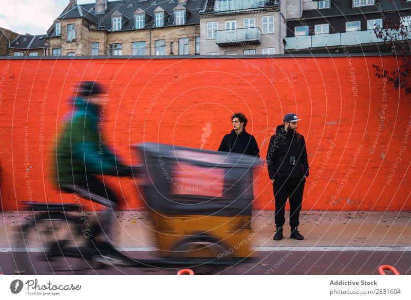 Zwei Männer an der orangefarbenen Wand Mann stehen Orange Zusammensein Straße gutaussehend Großstadt Jugendliche Stadt Lifestyle lässig Mode Stil Erwachsene