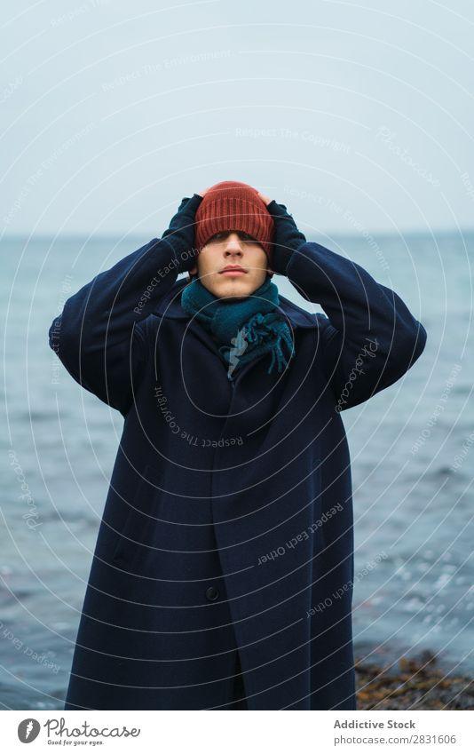 Mann setzt Hut auf Hut auf Augen Stil kalt Mantel ausrichten Meer