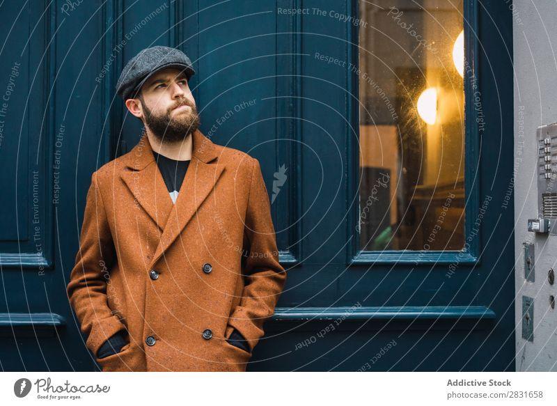 Nachdenklicher, stilvoller Mann an der Tür gutaussehend Großstadt Stil Mantel Hut Mütze Fürsorge besinnlich Straße Jugendliche Stadt Lifestyle lässig Mode