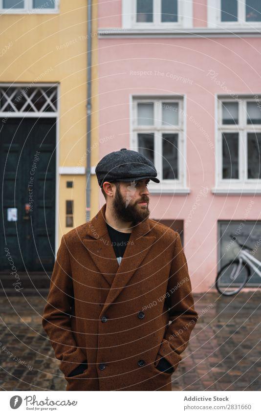 Bartiger Mann in Mantel gutaussehend Großstadt Stil Mütze Vollbart Hut Straße Jugendliche Stadt Lifestyle lässig Mode Erwachsene modern Mensch trendy