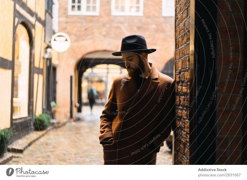 Stilvoller Mann, der sich an die Wand lehnt. gutaussehend Großstadt Mantel Hut anlehnen Straße Jugendliche Stadt Lifestyle lässig Mode Erwachsene modern Mensch