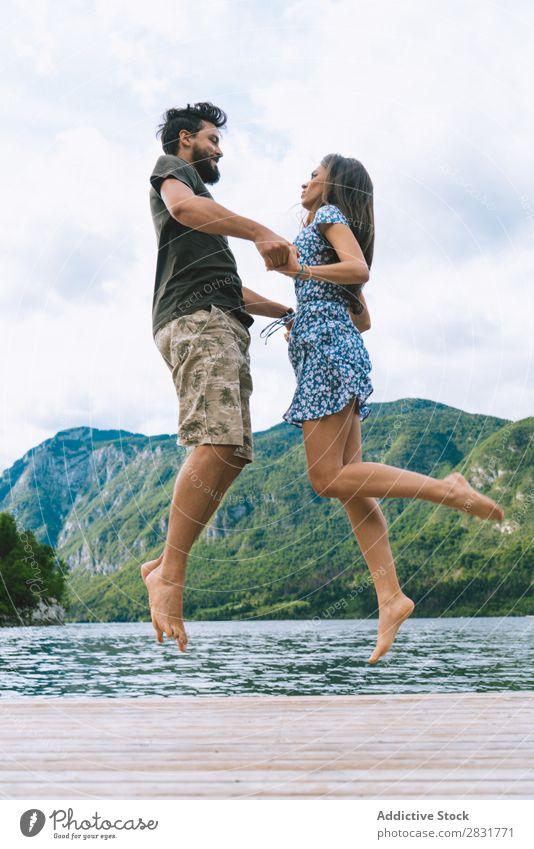 Paar Springen auf dem Pier Anlegestelle Freude See Berge u. Gebirge springen Glück Liebe Zusammensein Natur Sommer Wasser Jugendliche Frau