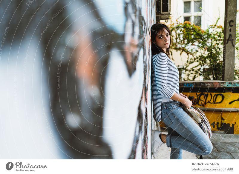 Frau, die sich an die Wand lehnt und auf die Kamera schaut. Mensch lässig Körperhaltung selbstbewußt Stil Stadt Accessoire Rucksack anlehnen reisend ernst