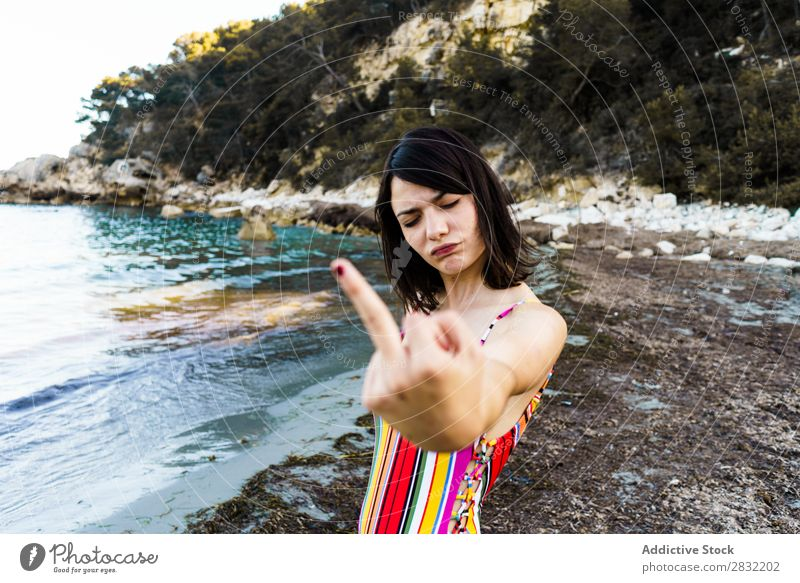 Ausdrucksstarkes Mädchen am Strand mit Mittelfinger Frau gestikulieren Provokation angriffslustig Sommer missbräuchlich Gefühle Jugendliche