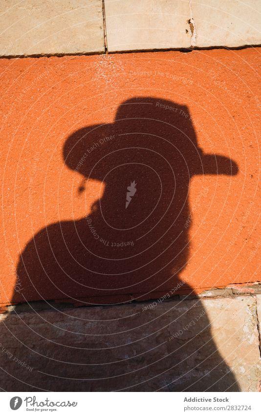 Männlicher Schatten mit Pistole an der Wand Mann Cowboy Westen Silhouette wild Western Umrisslinie Hut hell Risiko Sonnenlicht Kontrast gefährlich Stil