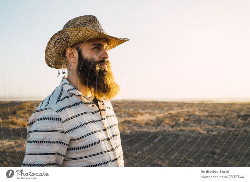 Bartiger Mann mit Hut gegen Sonnenlicht bärtig Cowboy Stil selbstbewußt Natur Porträt Länder maskulin ernst Strohhut Outfit Außenaufnahme Ausdruck Reisender