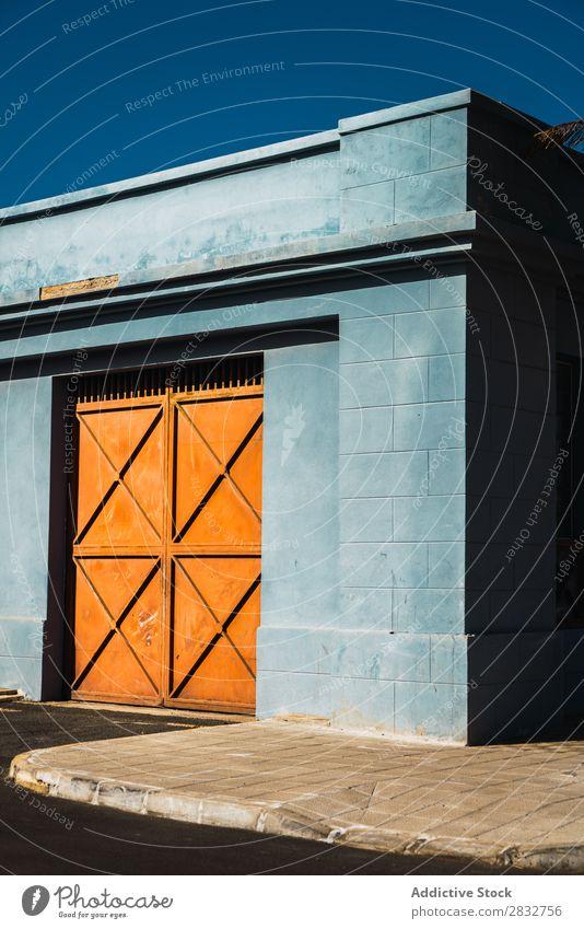 Orangefarbene Tore in blauer Wand Außenseite Metall Gebäude Konsistenz mehrfarbig Hauseingang Farbe hell Tag Architektur Stahl Tür Fassade Strukturen & Formen