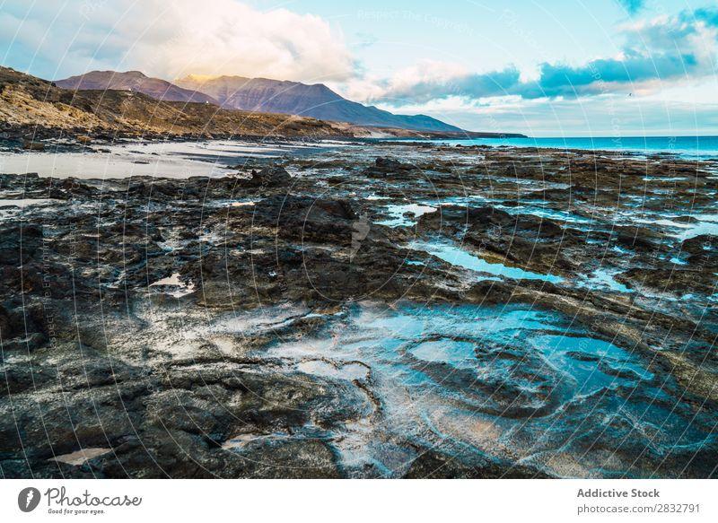 Erstaunliche Uferformationen mit Bergen im Hintergrund Küste Schlamm Formation Meer Landschaft schlammig Felsen Wildnis Beautyfotografie friedlich Strand