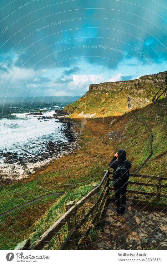 Tourist am Aussichtspunkt stehend Küste Seeküste Felsen Meer Landschaft Mensch Schüsse Strand Natur Wasser natürlich Meereslandschaft Stein schön grün Gras