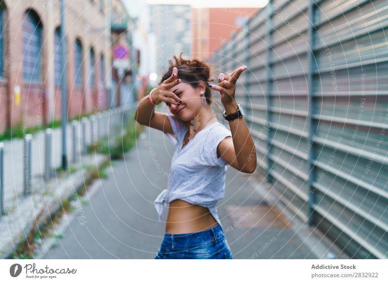 Stylisches ausdrucksstarkes Mädchen, das auf der Straße posiert. Frau Stil spielerisch gestikulierend Jugendliche Ferien & Urlaub & Reisen zeigen