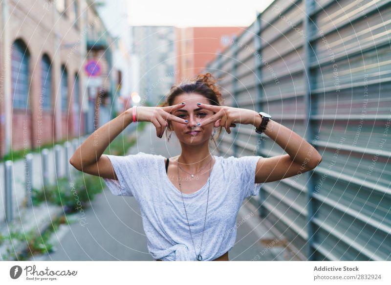 Stylisches ausdrucksstarkes Mädchen, das auf der Straße posiert. Frau Stil spielerisch gestikulierend Jugendliche Ferien & Urlaub & Reisen zeigen Stadt heiter