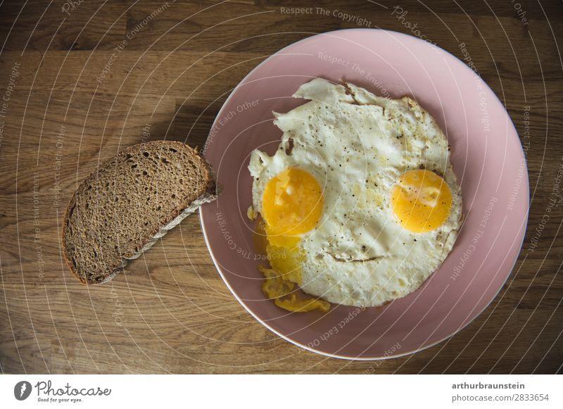 Spiegelei Gesicht mit Brotscheibe Lebensmittel Ei Ernährung Frühstück Geschirr Teller Gesundheit Gesunde Ernährung Koch Holz Essen authentisch braun gelb rosa