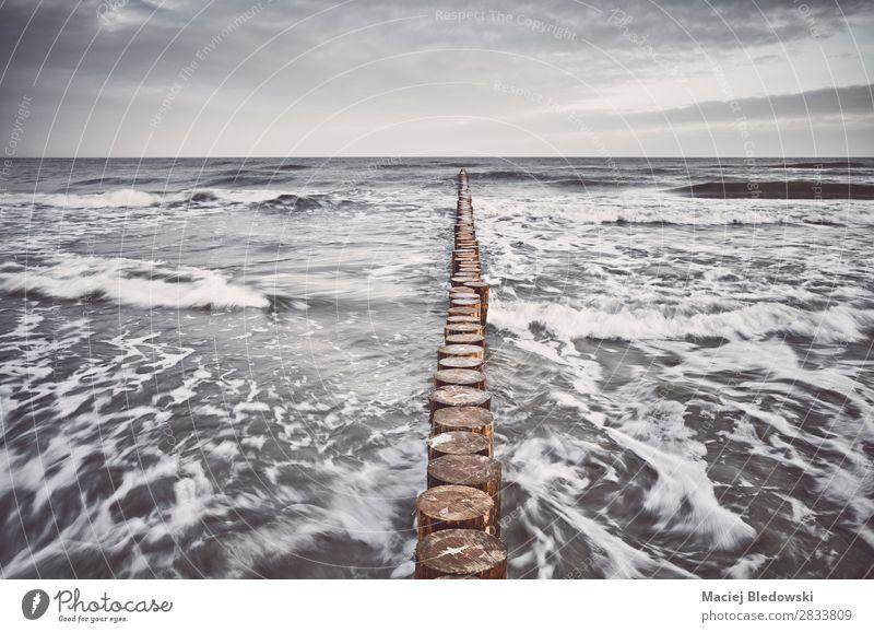 Farbig getöntes Bild einer hölzernen Wellenbrecheranlage Ferien & Urlaub & Reisen Ferne Freiheit Strand Meer Insel Natur Himmel Wolken Horizont Unwetter Wind