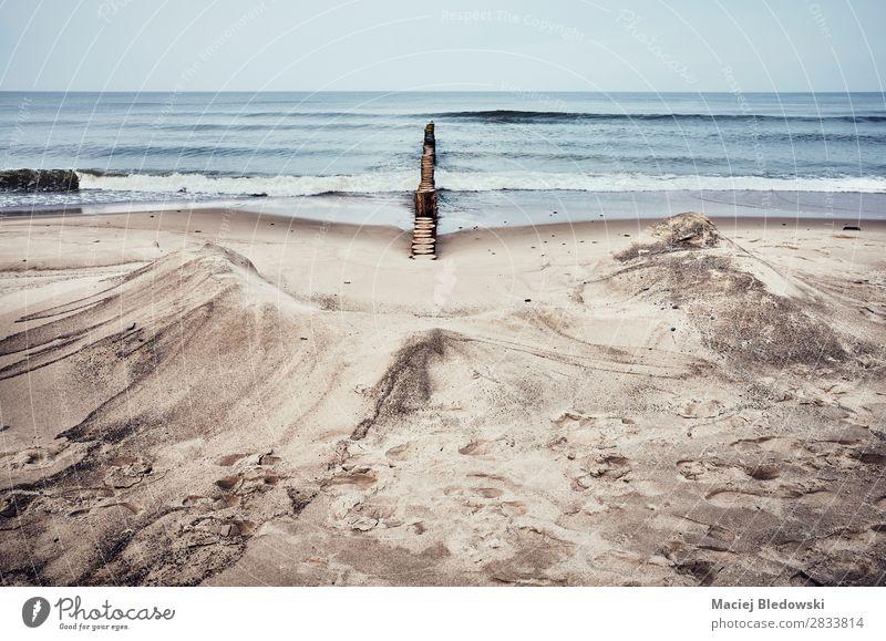 Sandstrand mit Holzlehne. Ferien & Urlaub & Reisen Abenteuer Ferne Freiheit Strand Meer Wellen Natur Himmel Horizont schlechtes Wetter Unwetter Traurigkeit
