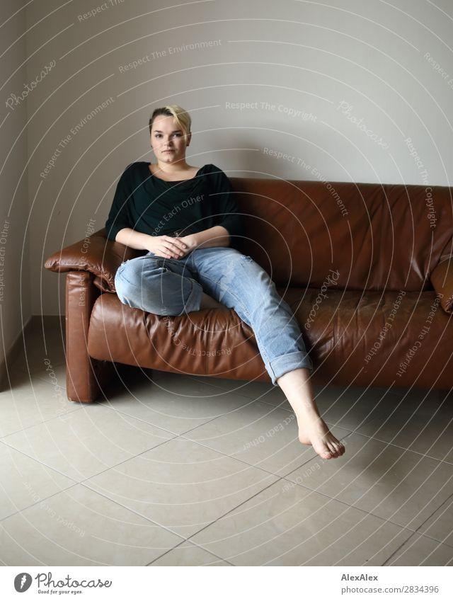 Junge Frau sitzt auf der Couch Stil Zufriedenheit Sofa Raum Jugendliche 18-30 Jahre Erwachsene Jeanshose Piercing Barfuß blond kurzhaarig sitzen ästhetisch