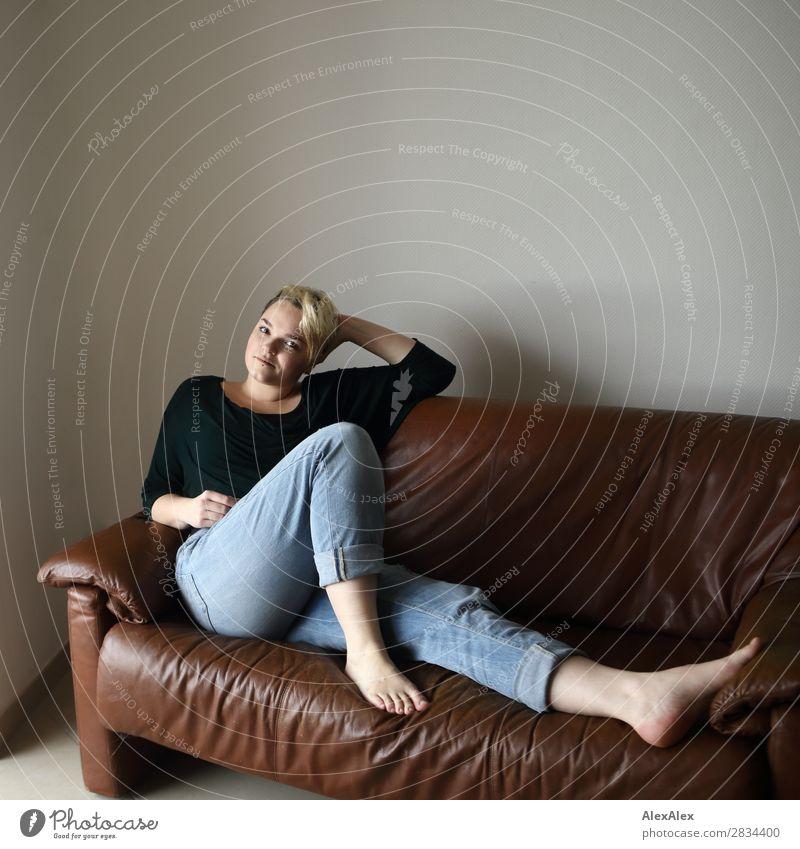 Junge Frau sitzt auf der Couch Stil Freude schön Zufriedenheit Sofa Raum Jugendliche 18-30 Jahre Erwachsene Jeanshose Barfuß blond kurzhaarig Blick sitzen