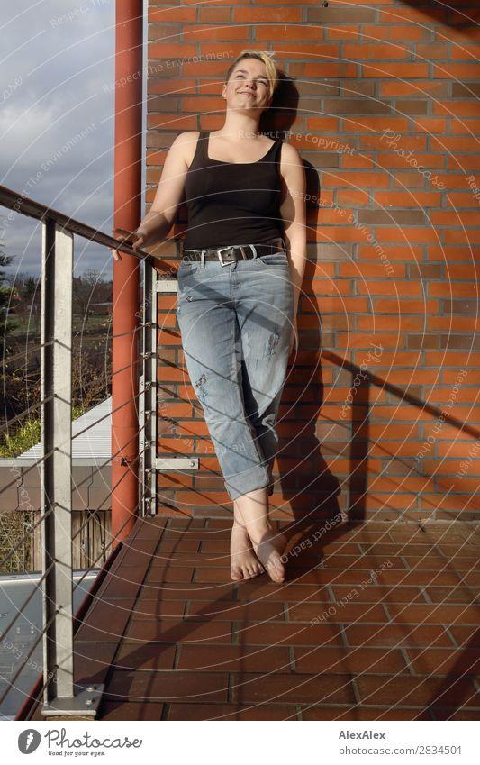 Junge Frau auf sonnigem Balkon Jugendliche Stadt schön Freude 18-30 Jahre Erwachsene natürlich feminin Glück Zufriedenheit blond Lächeln ästhetisch stehen