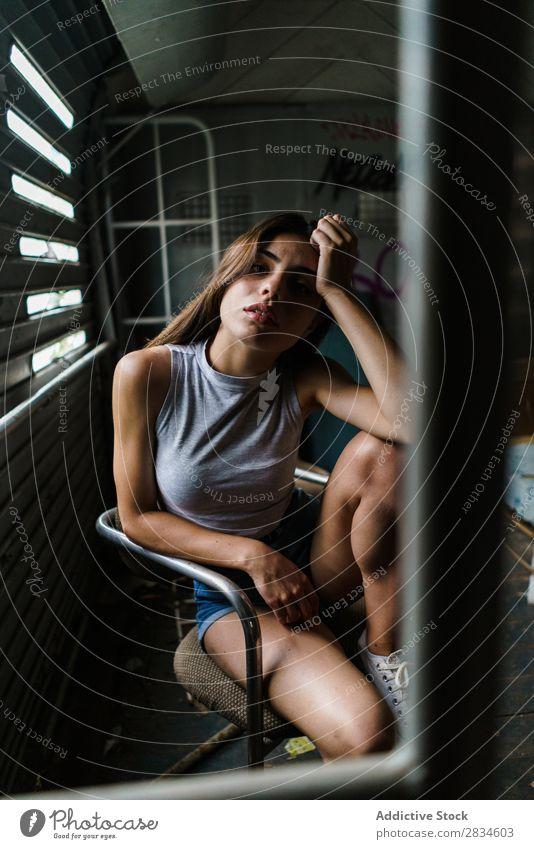Frau, die in einem verfallenen Haus sitzt. Fenster Gebäude sitzen Verlassen alt dreckig kaputt Stadt Schaden Architektur Graffiti hübsch Jugendliche Wand