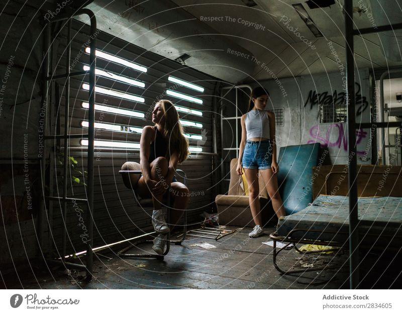 Frauen in verfallenem Haus Fenster Gebäude sitzen Verlassen alt dreckig kaputt Stadt Schaden Architektur Graffiti hübsch Jugendliche Wand Schlafzimmer Grunge