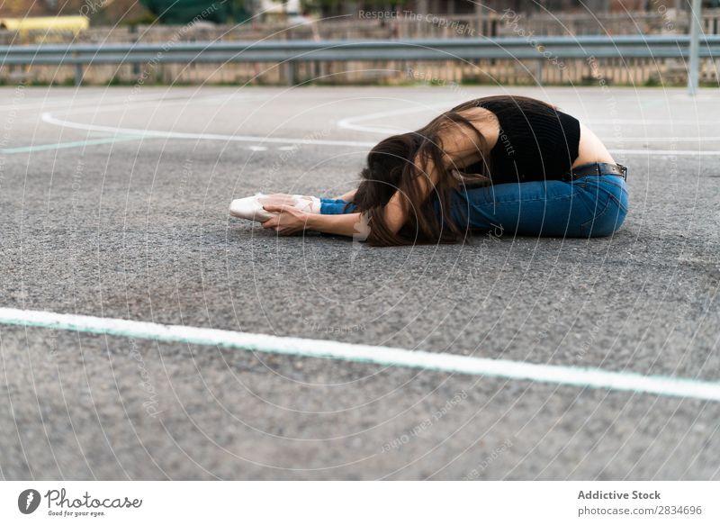 Frau, die auf einem Spielplatz liegt. Balletttänzer Tanzen lügen Boden Asphalt Pose Straße Entwurf Großstadt Stadt Mädchen Tänzer Ballerina elegant schön