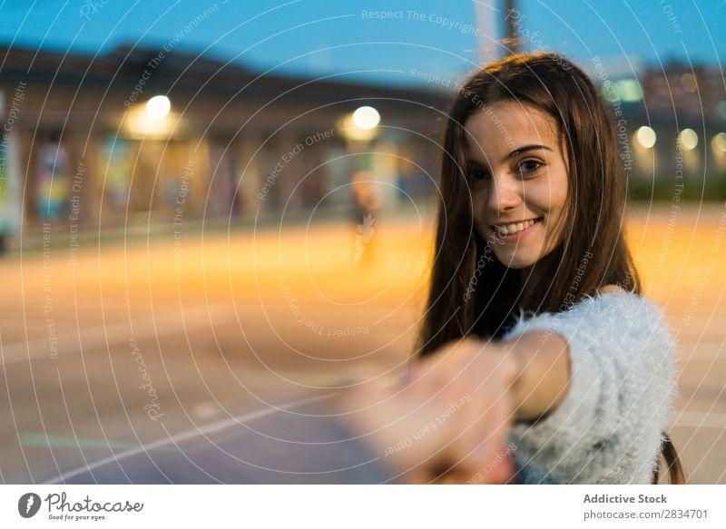 """Junge Frau macht eine """"Follow me""""-Geste und schaut in die Kamera. hübsch Abend Mädchen schön mir folgen gestikulieren in die Kamera schauen jung Schönheit"""