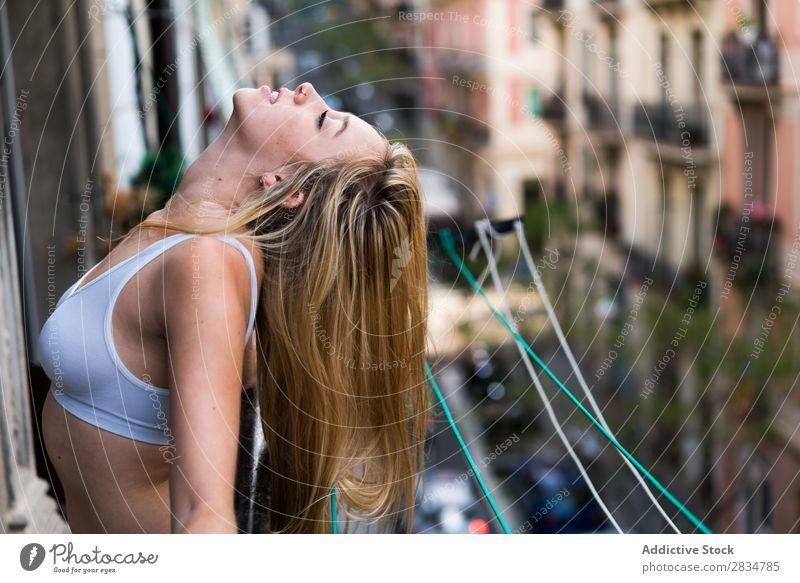 Sexy junge Frau, die auf dem Balkon atmet. Mensch Haus Jugendliche Erotik Mädchen Kaukasier Glück heimwärts hübsch schön heiter Erholung Beautyfotografie weiß