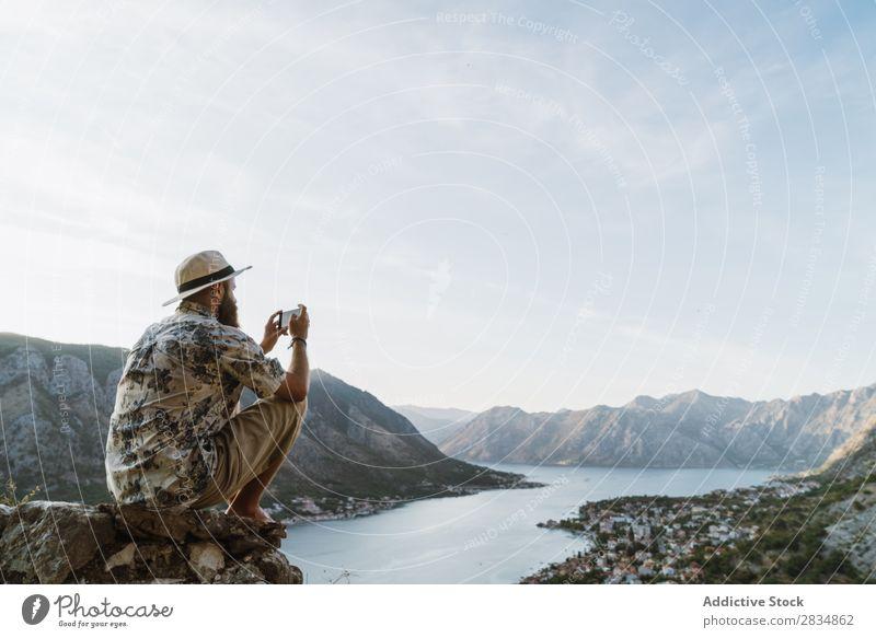 Ein Mann, der Aufnahmen von der Stadt macht. Berge u. Gebirge Fluss Mensch Schüsse nehmen Tourist Dorf Aussicht Weg Landschaft Ferien & Urlaub & Reisen Natur