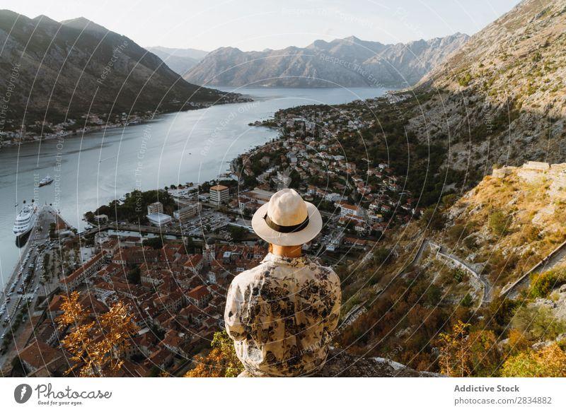 Tourist schaut auf die Stadt am Flussufer. Berge u. Gebirge Mann Mensch Dorf Aussicht