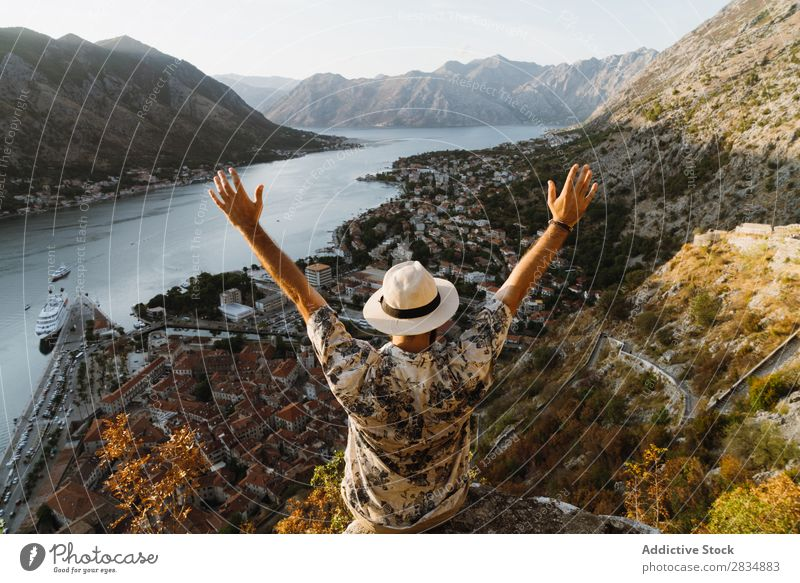 Tourist schaut auf die Stadt am Flussufer. Berge u. Gebirge Mann Mensch Dorf Aussicht Weg Landschaft Ferien & Urlaub & Reisen Hände hoch Natur Tourismus schön