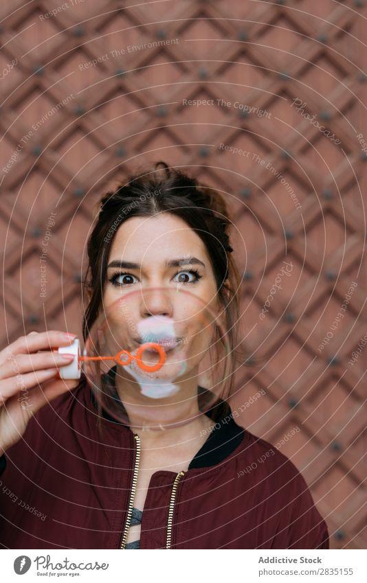 Überraschte Frau, die Blasen bläst. blasen überrascht Backstein lässig Wand Glück Mensch Halt Kaukasier Jugendliche Erwachsene Lifestyle Textfreiraum heiter