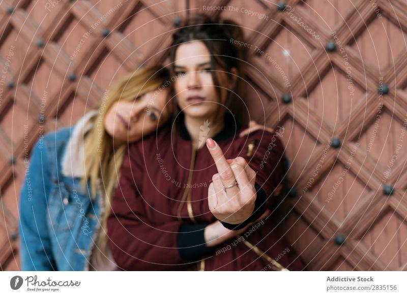 Frauen an der Wand gestikulierend mit dem Mittelfinger fick dich Paar Glück Homosexualität alternativ Liebe Mensch Kaukasier Jugendliche Partnerschaft schön