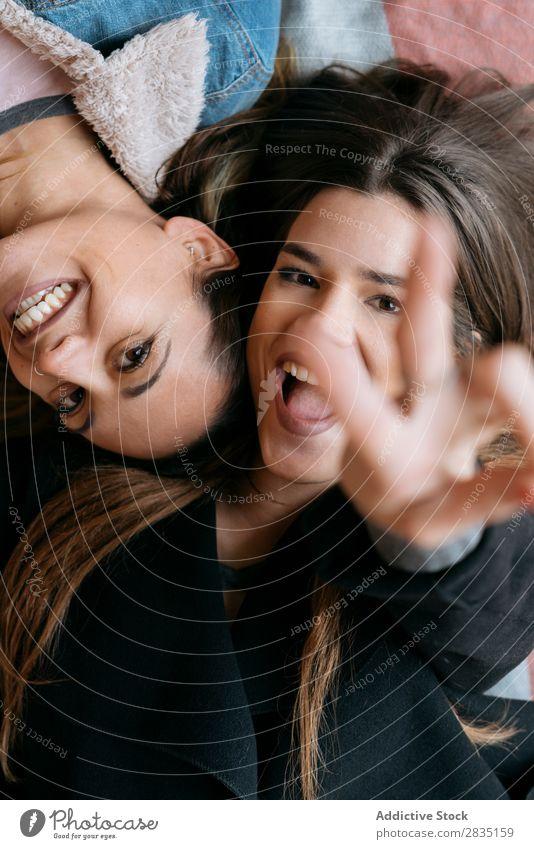 Glückliches Frauenpaar beim Anblick der Kamera gestikulieren zwei Finger legen Paar Homosexualität alternativ Liebe Mensch Kaukasier Jugendliche Partnerschaft