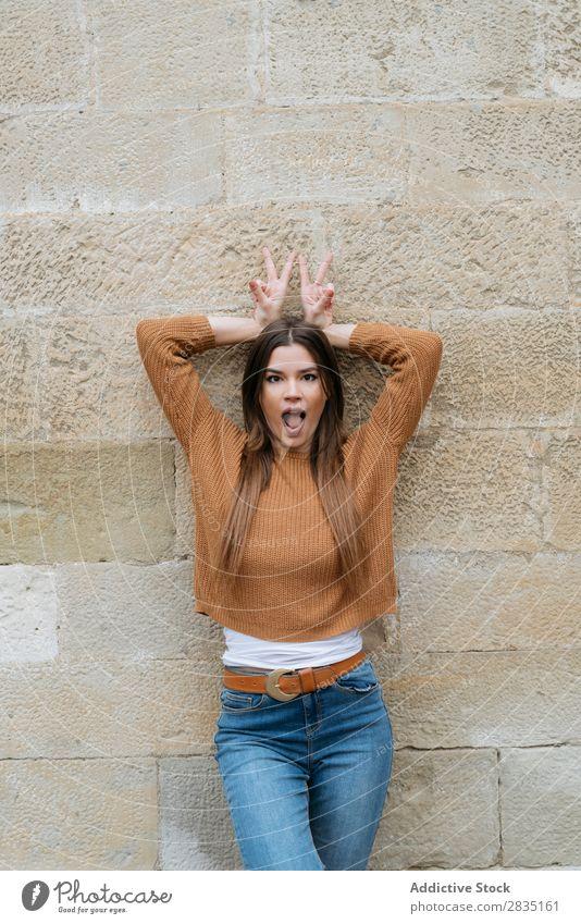 Frau mit geöffnetem Mund, die in der Nähe der Wand posiert. Mund geöffnet gestikulieren zwei Finger Glück Backstein Mensch Kaukasier Jugendliche schön
