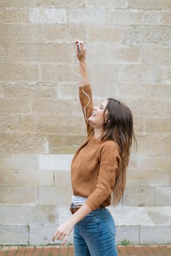 Glückliche Frau mit der Hand in den Kopfhörern Lächeln Telefon Backstein Wand Mensch
