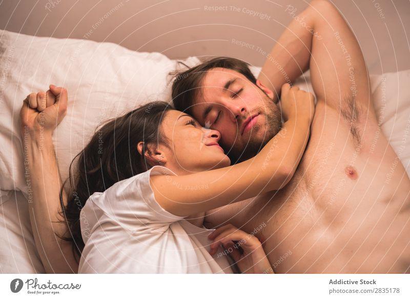 Frau, die auf einen schläfrigen Freund schaut. Paar Umarmen Mann strecken Morgen Liebe Jugendliche Partnerschaft Mensch 2 Bett Schlafzimmer Romantik