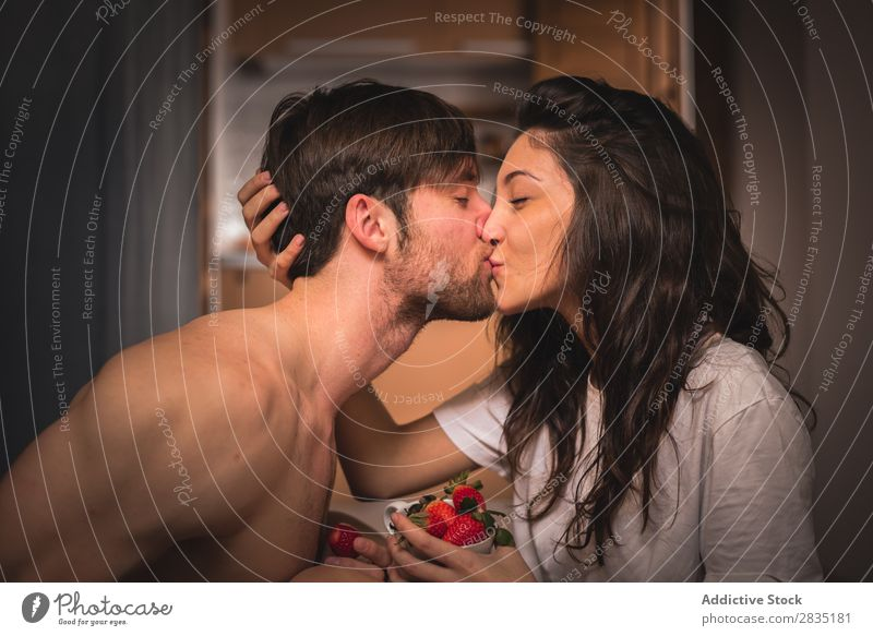 Ein Paar küsst sich mit Erdbeeren. Jugendliche Küssen Frau Mann Liebe Partnerschaft Augen geschlossen Beeren rot saftig Frucht Mensch 2 Romantik Zusammensein