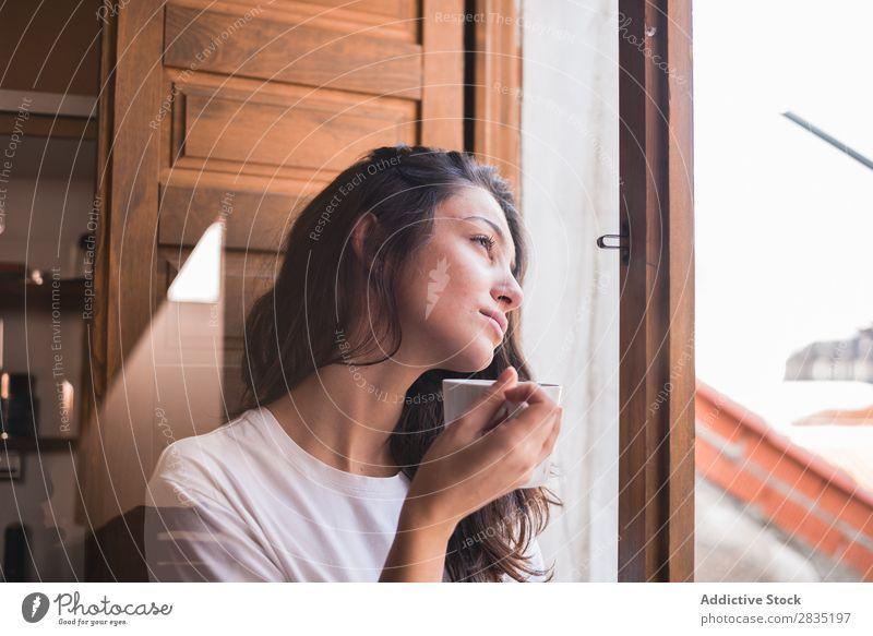 Nachdenkliche Frau mit einem Becher Tasse Fenster besinnlich träumen Fürsorge Blick trinken schön Jugendliche Beautyfotografie Mädchen Tee Kaffee heimwärts