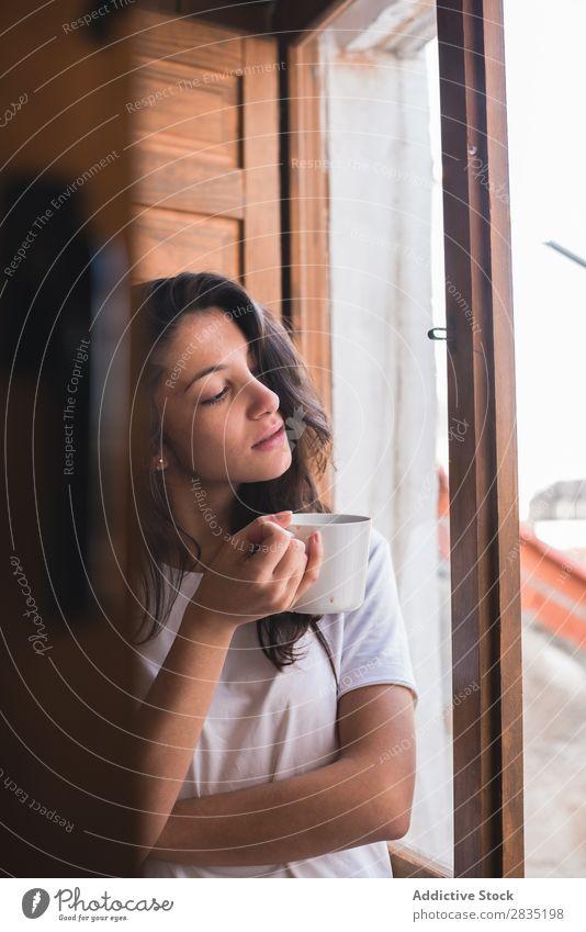 Junge hübsche Frau mit einer Tasse Fenster besinnlich träumen Fürsorge Blick Becher trinken schön Jugendliche Beautyfotografie Mädchen Tee Kaffee heimwärts