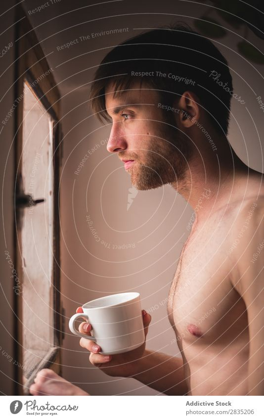 Schläfriger Mann mit einem Becher schläfrig Tasse Morgen Fürsorge Wegsehen besinnlich heiß trinken Denken Frühstück Lifestyle heimwärts Porträt Küche