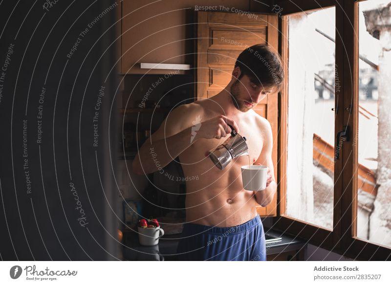 Mann, der einen Kaffee in die Tasse gießt. Gießen Morgen Füllung Fürsorge besinnlich Becher heiß trinken Denken Frühstück Lifestyle heimwärts Porträt Küche
