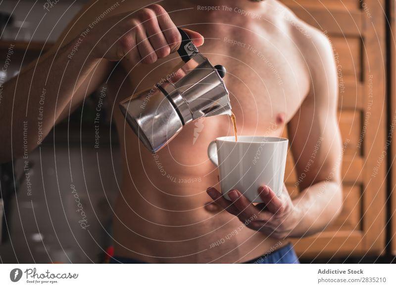 Hemdloser Mann beim Kaffee trinken Mensch Gießen Füllung Tasse Morgen Becher heiß Frühstück Lifestyle heimwärts frisch Koffein Topf eingießen Porträt Küche
