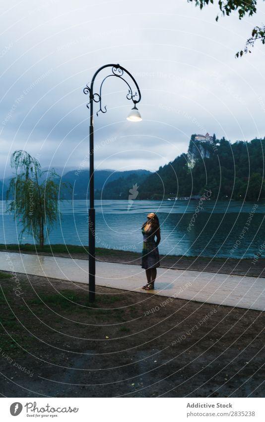 Frau, die auf den Laternenpfahl schaut. laufen See aufschauend Lampe Abend Küste