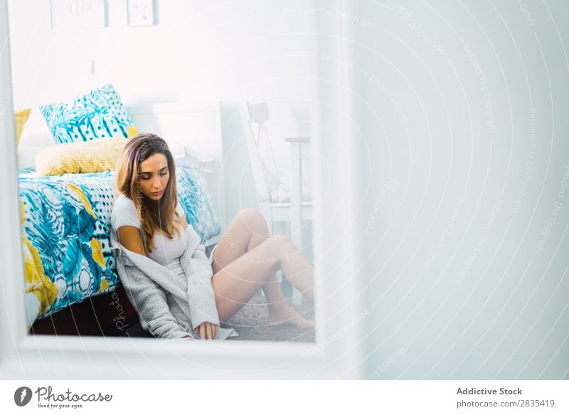 Hübsche Frau liest ein Buch auf dem Boden. heimwärts Jugendliche Körperhaltung sitzen lesen Bett