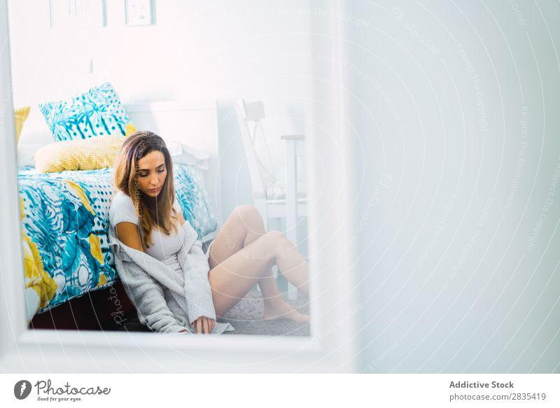 Hübsche Frau liest ein Buch auf dem Boden. hübsch heimwärts Jugendliche Körperhaltung sitzen lesen Bett Roman Literatur Porträt schön Lifestyle Beautyfotografie