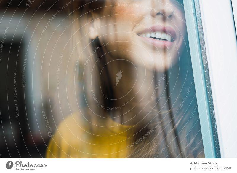 Beschneiden Sie die fröhliche Frau am Fenster. hübsch heimwärts Jugendliche durch das Fenster Lächeln heiter Glück Körperhaltung Porträt schön Lifestyle